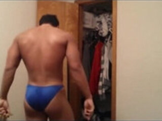 Young bodybuilder flexes his muscles in blue thong